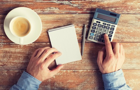 income: business, education, people and technology concept - close up of male hands with calculator, pen and notebook on table