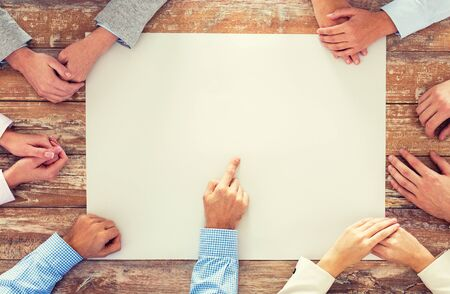 fingers on top: business, people and team work concept - close up of creative team sitting at table and pointing finger to blank paper in office