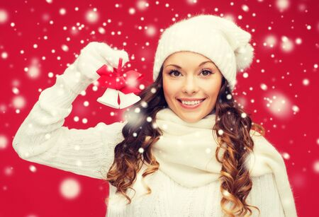 jingle bells: christmas, x-mas, winter, happiness concept - smiling woman in mittens and hat with jingle bells Stock Photo