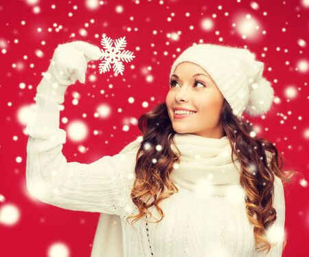 muffler: winter, people, happiness concept - woman in hat, muffler and gloves with big snowflake Stock Photo