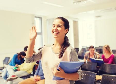 jovenes estudiantes: la educación, la escuela secundaria, gesto, trabajo en equipo y concepto de la gente - grupo de estudiantes sonrientes con libretas agitando la mano en el salón de conferencias