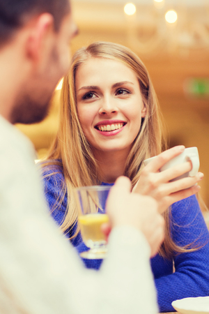 couple dating: people, leisure, dating and communication concept - happy couple dating and drinking tea at cafe or restaurant
