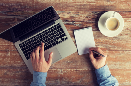 business, education, people and technology concept - close up of male hands with laptop and coffee cup taking notes to notebook by pen