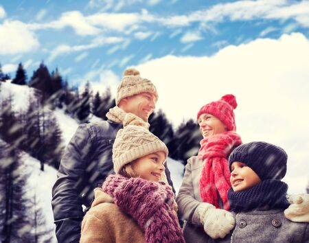 winter vacation: family, childhood, season and people concept - happy family in winter clothes over snowy mountains background