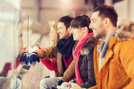 patinaje sobre hielo: la gente, la amistad, el deporte y el concepto de ocio - amigos felices viendo partido de hockey o patinaje artístico el rendimiento en pista de patinaje