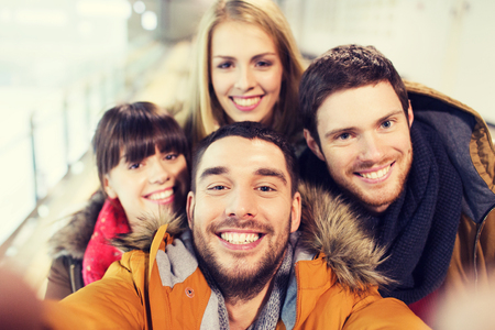 people, friendship, technology and leisure concept - happy friends taking selfie with camera or smartphone on skating rink Stock Photo