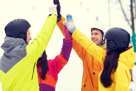 people having fun: winter, leisure, extreme sport, friendship and people concept - happy friends in helmets making high five gesture