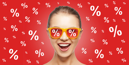 people, summer, shopping and sale concept - happy screaming teenage girl in shades over red background with percentage signs Banco de Imagens