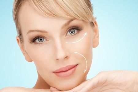 Schönheit, Menschen, Anti-Aging-Behandlung und plastische Chirurgie Konzept - schöne junge Frau mit Gesichtslifting Pfeile auf blauem Hintergrund Standard-Bild - 48379905
