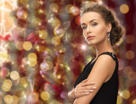 hollywood christmas: people, holidays, jewelry and glamour concept - beautiful woman wearing earrings over christmas lights background Stock Photo