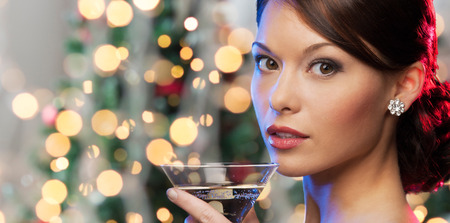 asian trees: party, drinks, holidays, luxury and celebration concept - woman face with cocktail over christmas tree lights