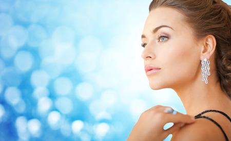 mensen, vakantie, juwelen, luxe en glamour concept - mooie vrouw met mooie diamanten oorbellen op blauwe achtergrond verlichting