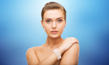 bride bangle: beauty, luxury, people, holidays and jewelry concept - beautiful woman with pearl earrings and bracelet over blue background
