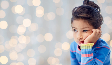 people, childhood and emotions concept - sad and disappointed or bored little girl over holidays lights background