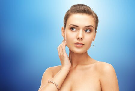 bangle: beauty, luxury, people, holidays and jewelry concept - beautiful woman wearing gold earrings and bracelet over blue background