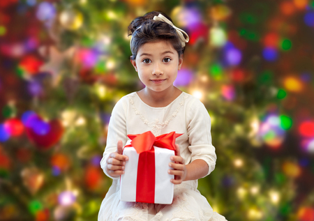 asian children: holidays, presents, christmas, childhood and people concept - smiling little girl with gift box over lights background Stock Photo
