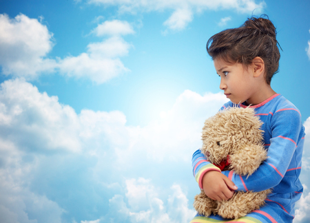hispanic girl: childhood, sadness, loneliness and people concept - sad little girl with teddy bear toy over blue sky and clouds background Stock Photo