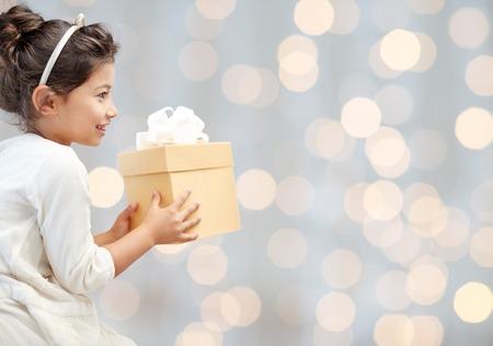 infancia: días de fiesta, los presentes, navidad, la infancia y concepto de la gente - una sonrisa de niña con caja de regalo sobre fondo de las luces
