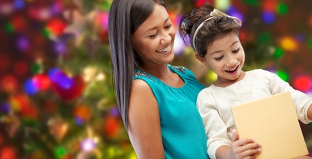 asian preteen: holidays, birthday, family, childhood and people concept - happy mother and little girl with gift over lights background Stock Photo