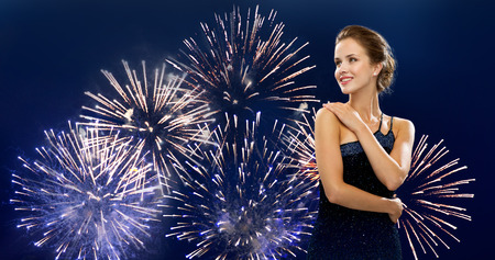 hollywood christmas: people, holidays and glamour concept - happy beautiful woman in evening dress over firework on dark blue background