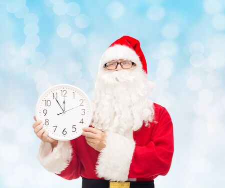 twelve month old: christmas, holidays and people concept - man in costume of santa claus with clock showing twelve over blue lights background Stock Photo
