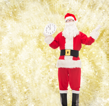 reminding: christmas, holidays and people concept - man in costume of santa claus with clock showing twelve over yellow lights background