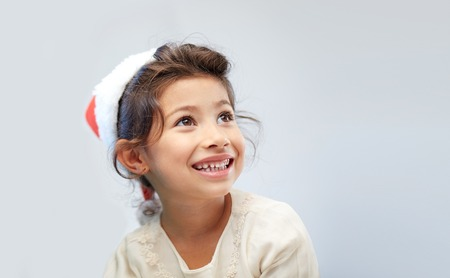 asian preteen: christmas, holidays, childhood and people concept - happy little girl in santa hat over gray background