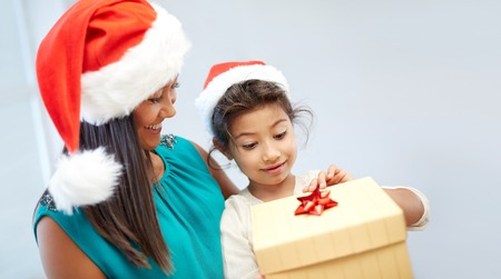single family: christmas, holidays, family, childhood and people concept - happy mother and little girl in santa hats opening gift box at home