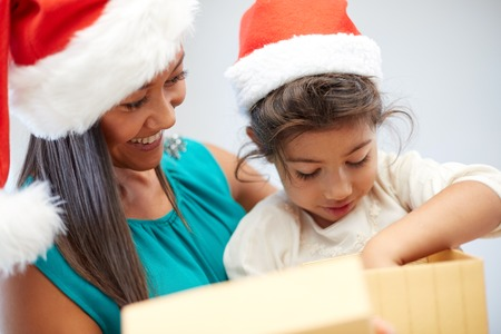 asian preteen: christmas, holidays, family, childhood and people concept - happy mother and little girl in santa hats opening gift box at home