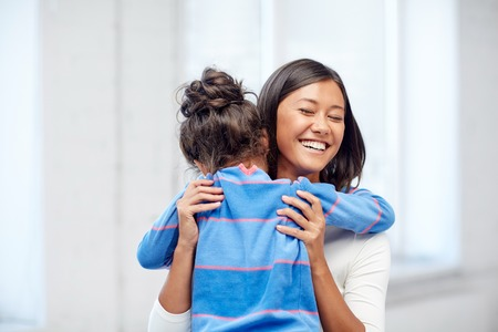 preteen asian: family, children, love and happy people concept - happy mother and daughter hugging at home Stock Photo