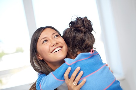 single mother: family, children, love and happy people concept - happy mother and daughter hugging at home Stock Photo