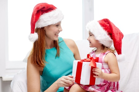 childhood: christmas, holidays, family, childhood and people concept - happy mother and little girl in santa hats with gift box at home Stock Photo