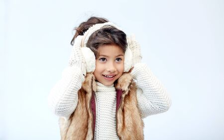 asian preteen: winter, people, happiness concept - happy little girl wearing earmuffs