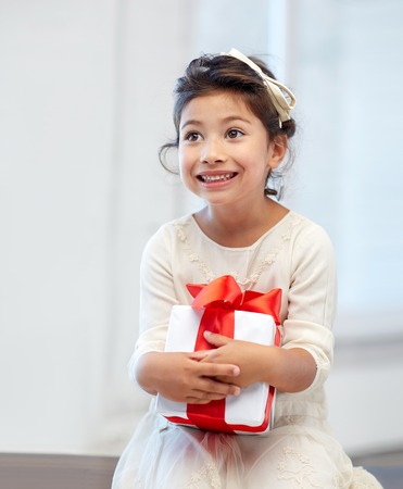 holidays, presents, christmas, childhood and people concept - smiling little girl with gift box at home