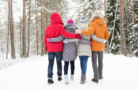 and in winter: love, relationship, season, friendship and people concept - group of happy men and women walking in winter forest