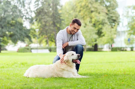 golden retriever: family, pet, animal and people concept - happy man with labrador retriever dog walking in city park
