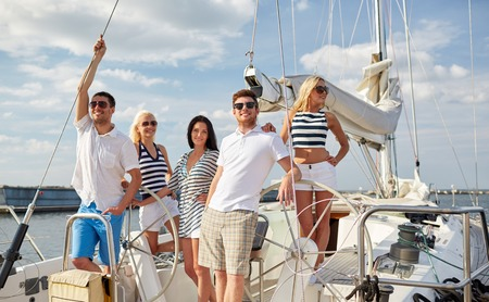 sail: vacation, travel, sea, friendship and people concept - smiling friends sailing on yacht