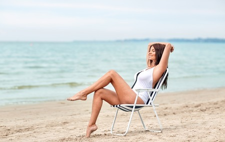 relaxing beach: summer vacation, tourism, travel, holidays and people concept - smiling young woman sunbathing in lounge or folding chair on beach