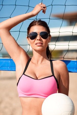 female volleyball: summer vacation, sport and people concept - young woman with volleyball ball and net on beach