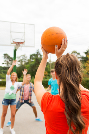 playground basketball: summer vacation, sport, games and friendship concept - group of happy teenagers playing basketball outdoors from back