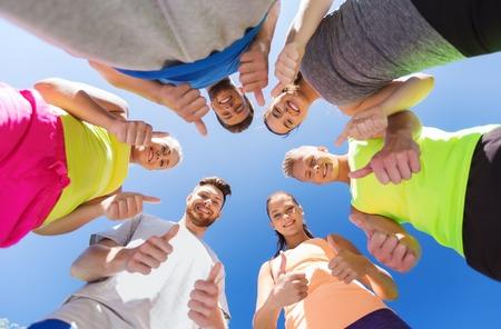 circulo de personas: fitness, deporte, la amistad y el concepto de estilo de vida saludable - grupo de amigos adolescentes felices en círculo al aire libre que muestra los pulgares para arriba