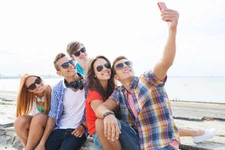 friends fun: friendship, leisure, summer, technology and people concept - group of happy friends with smartphone taking selfie outdoors Stock Photo