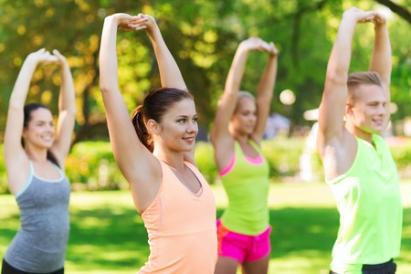 boot camp: fitness, sport, friendship and healthy lifestyle concept - group of happy teenage friends or sportsmen exercising and stretching hands up at boot camp