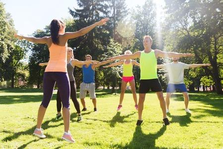 フィットネス: フィットネス、スポーツ、友情、健康的なライフ スタイル コンセプト - 幸せな 10 代の友人やブート キャンプでエクササイズのスポーツマンのグループ