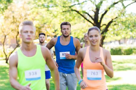 chicas adolescentes: fitness, deporte, la amistad, la raza y el concepto de estilo de vida saludable - grupo de amigos o deportistas adolescentes felices corriendo maratón con números de placa al aire libre