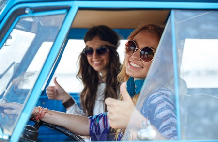 thumbs: summer holidays, road trip, vacation, travel and people concept - smiling young hippie women driving and showing thumbs up gesture in minivan car