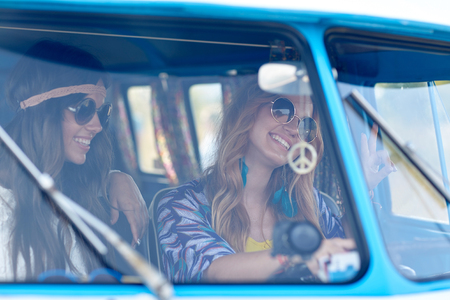 peace: summer holidays, road trip, vacation, travel and people concept - smiling young hippie women driving minivan car and showing peace gesture