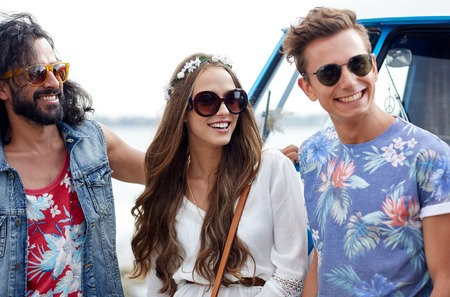 fashion girl: summer holidays, road trip, vacation, travel and people concept - smiling young hippie friends over minivan car