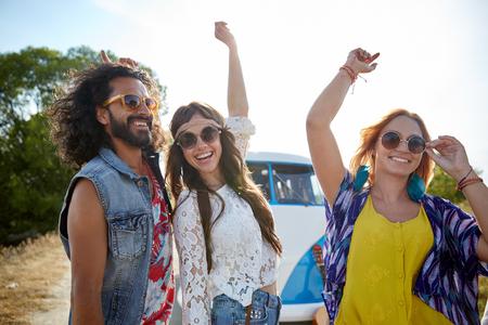 parejas felices: naturaleza, verano, la cultura juvenil y la gente concepto - amigos felices hippie j�venes bailando sobre un coche monovolumen al aire libre