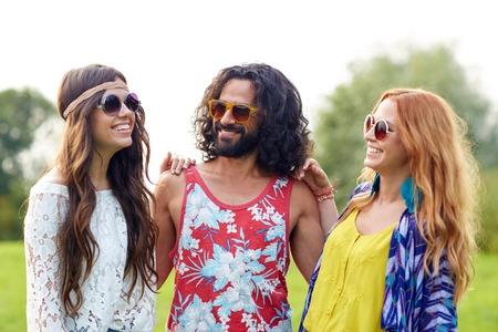 teenage girl happy: nature, summer, youth culture and people concept - smiling young hippie friends in sunglasses talking outdoors Stock Photo